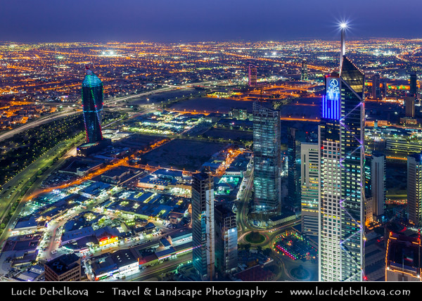 """Middle East - GCC - Kuwait - Kuwait City - City's Modern Skyline with highrise buildings including Al Tijaria Tower - Kuwait Trade Center inspired by a spiral or helix, body of the tower """"twists"""" by 80 degrees as it climbs to 218.2 m / 716 ft at Dusk - Twilight - Blue Hour - Night"""