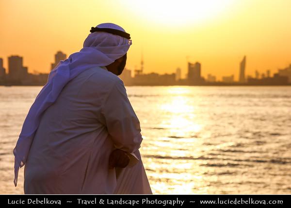 Middle East - GCC - Kuwait - Salmiya corniche - Arabian Gulf Street - Sea front with Kuwait City skyline and local man in traditional arabic dress dishdasha during Sunset