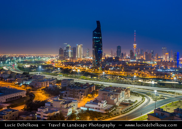 "Middle East - GCC - Kuwait - Kuwait City - City's Modern Skyline with highrise buildings including Al Tijaria Tower - Kuwait Trade Center inspired by a spiral or helix, body of the tower ""twists"" by 80 degrees as it climbs to 218.2 m / 716 ft at Dusk - Twilight - Blue Hour - Night"