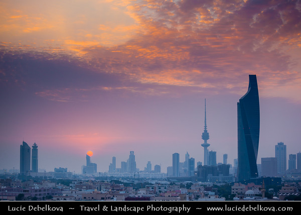 "Middle East - GCC - Kuwait - Kuwait City - City's Modern Skyline with highrise buildings including Al Tijaria Tower - Kuwait Trade Center inspired by a spiral or helix, body of the tower ""twists"" by 80 degrees as it climbs to 218.2 m / 716 ft - Sunset"