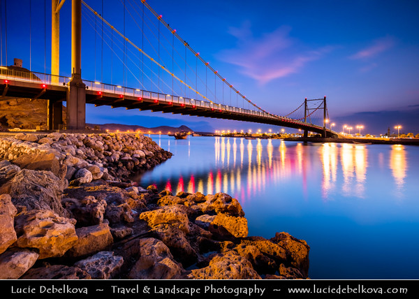 Middle East - Sultanate of Oman - Ash Sharqiyah Region - Sur - صور‎ - One of ancient Omani maritime cities & important destination point for sailors on coast of Gulf of Oman - Cityscape with modern Khour Al Batah Suspension Bridge at Dusk - Blue Hour - Night - Twilight