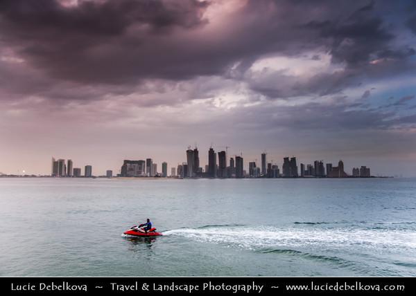 Middle East - Qatar - Doha - الدوحة - ad-Dawḥa - ad-Dōḥa - New and Modern Skyline with Sky High Skyscrapers along the Corniche and Qatari man on the Jet Ski