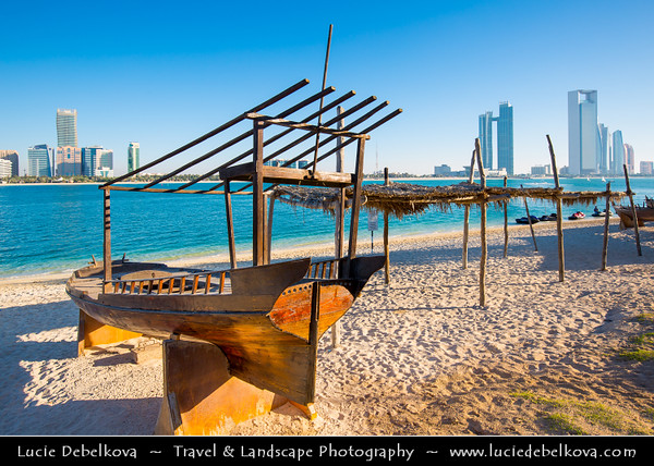Middle East - GCC - United Arab Emirates - UAE - Abu Dhabi - Traditional wooden boats on the crystal clear waters of corniche in front of brand new modern skyline with sky high skyscrapers