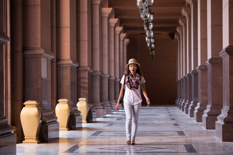 A tourist walks along the portico of the Emirates Palace hotel in Abu Dhabi, UAE.