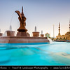 Middle East - GCC - United Arab Emirates - UAE - Emirate of Fujairah - Fujairah - Fountain with Arabic Coffee Pot Statue Roundabout with two minaret mosque behind