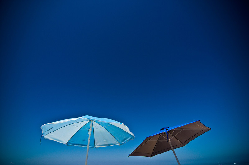 Title: Blue Umbrelas<br /> Date: August 2011<br /> Cape Cod MA - Two umbrellas along the beach.