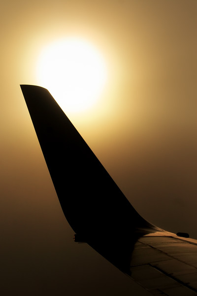 The tip of an aeroplane wing silhoetted against the morning sun while flying through cloud.