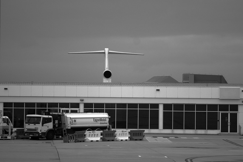 A plane on the tarmac behind a building.  Melbourne airport.