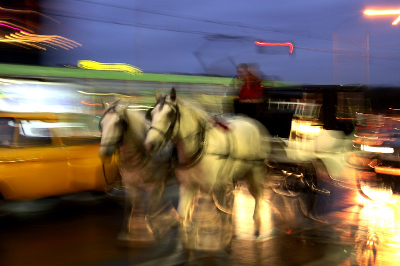 A horse-drawn carriage passes Flinders St Station. Melbourne, Victoria.