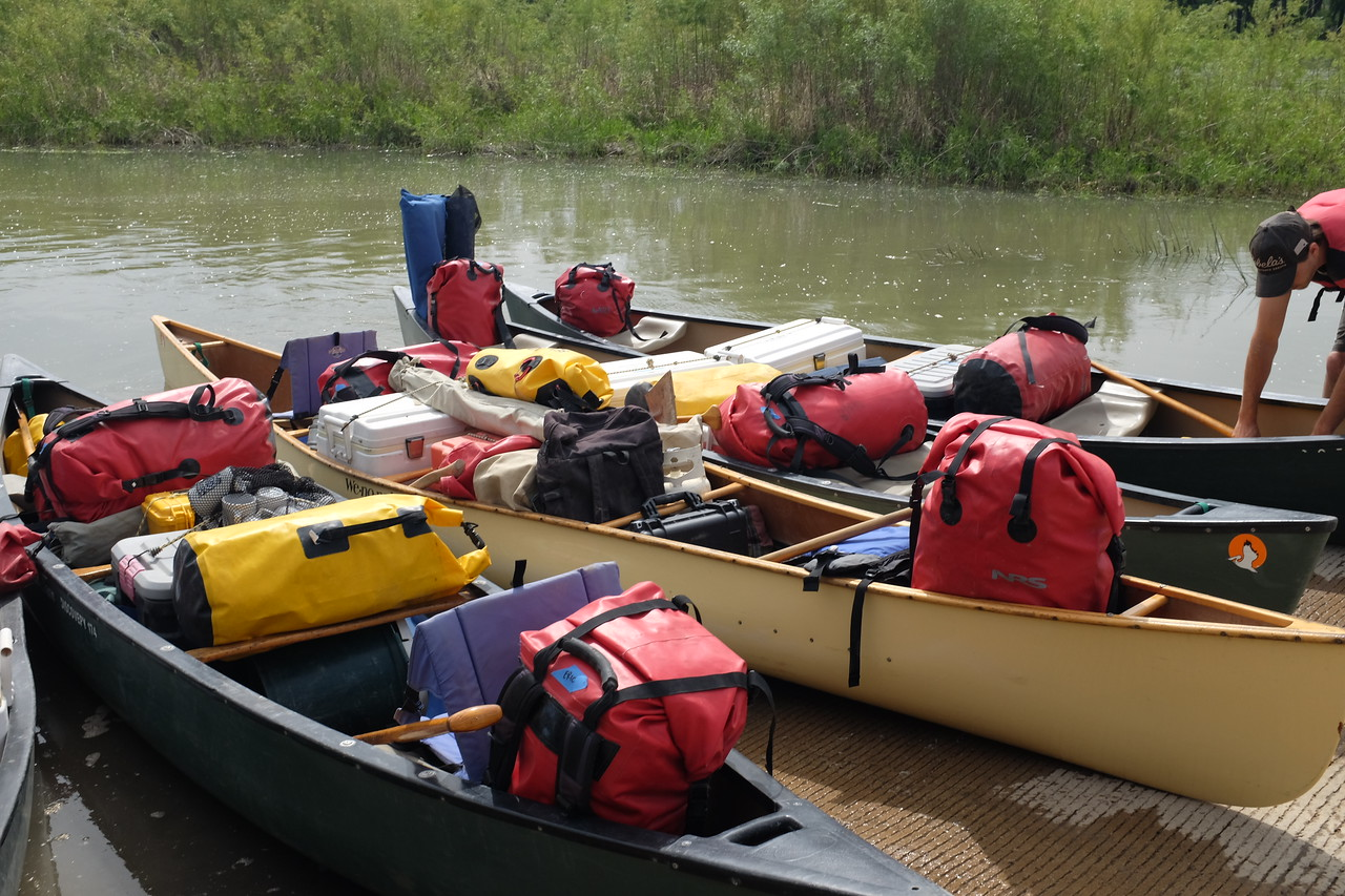 Balance -- both lateral and longitudinal -- is critical in a canoe. Notice how the large, red bags serve as backrests.