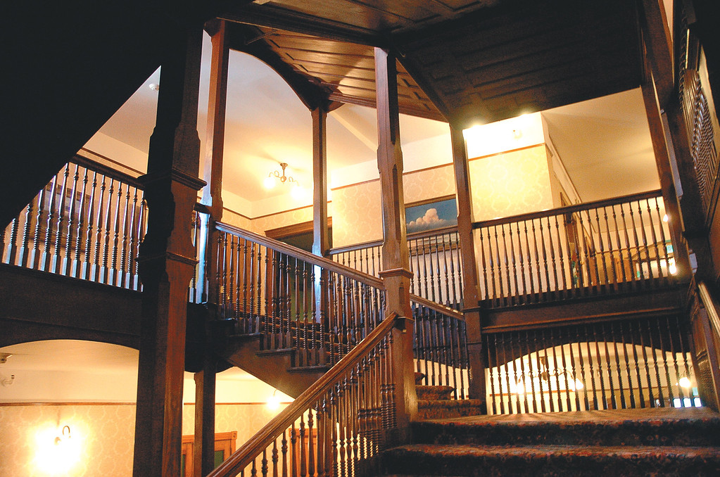 . A wooden staircase makes its way up all flights in the middle of the Mohonk Mountain House.