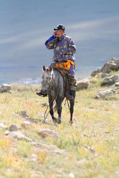 Love this image of the young Mongolian kid riding his horse, in a traditional del, talking on his cell phone.  Classic.