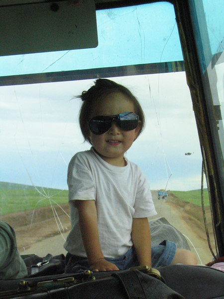 Kid on the bus to Ulaanbaatar.  Grandchild of the driver. This kid had fun throwing all the trash out the window.  2 points for him! 0 points for the environment.