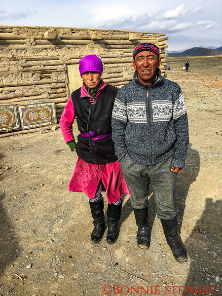"""Mr. Ardak and his wife in front of their winter  home.  Cj in the distance brining in the plastic toilet seat cover for covering the """"hole"""""""