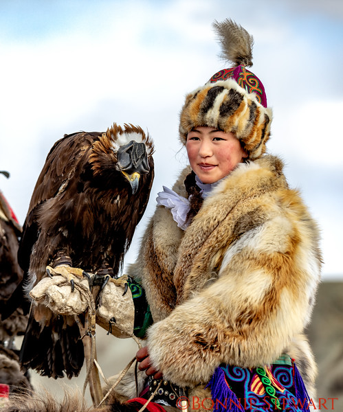 "A young women participating in the Altai Nomad Games 2018 as an Eagle Huntress.  Only recently, since the movie was released ""Eagle Huntress"" have women started to be training in Eagle Hunting and competing in the sport.  The movie was filmed in Mongolia and starred Aishlapan, a young Mongolia woman."
