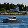The Monhegan Island ferry passes a local lobster boat with the Marshall Point Light in the background.