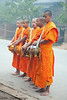 "Lao Monks Give A Blessing To A Home On Their Daily Alms Walk - ""Tak Bart"" After Accepting Food From the Occupants, Ban Khone, Luang Nam Tha Province, Lao People's Democratic Republic"