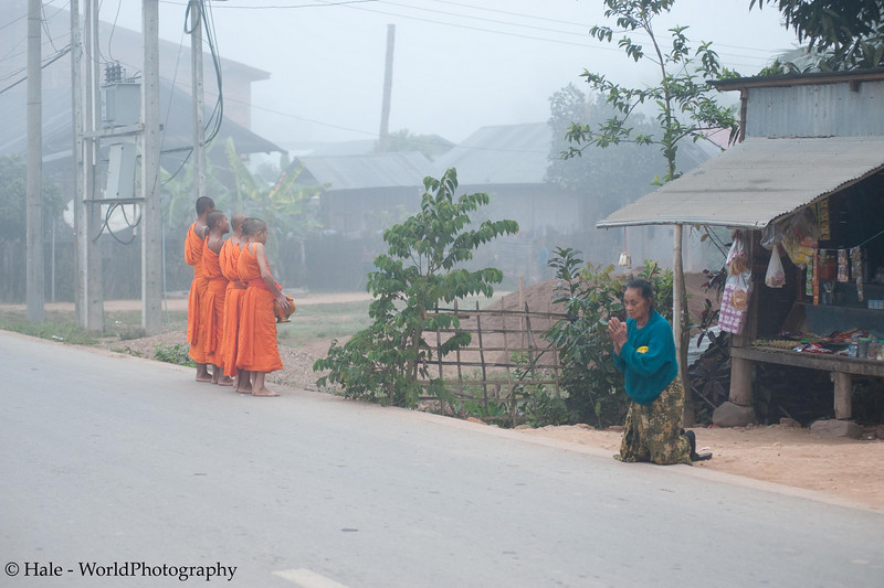 """Lao Monks Give A Blessing To A Home On Their Daily Alms Walk - """"Tak Bart"""" After Accepting Food From the Occupants, Ban Khone, Luang Nam Tha Province, Lao People's Democratic Republic"""