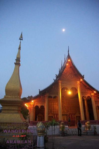 The moon shining over a temple as the sun comes up