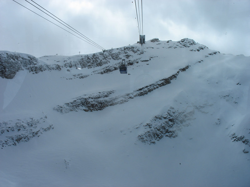 a long shot of a gondola descending. Note the electric poles at the peak for a sense of the scale.