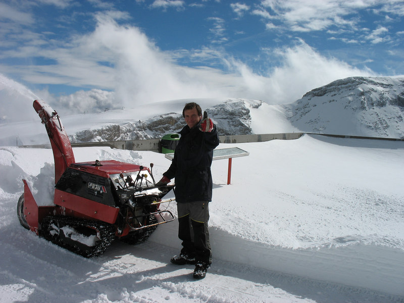 A man operating the snowblower to allow us to read the captions of the mountains. The signboard is visible behind him.