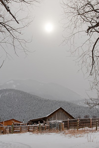 the sun peers weakly through a snow storm on a cold sub freezing day.  a barn sits in the foreground with mountains behind.
