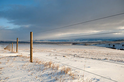 a fence marks the boundary of a montana ranch.  beyond the fence the plain is extends to the mountains in the background.