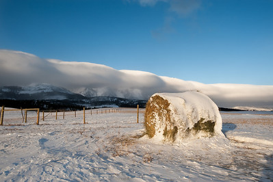 a hay bail is lit up by the early morning sun on a montana ranch.  a cloud wall looms in the background as an omen of the coming snow.