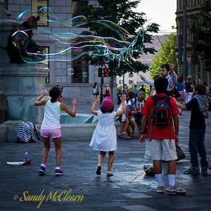 Children play while a street performer blows bubbles in the square at Place d'Armes in front of the Notre-Dame Basilica.