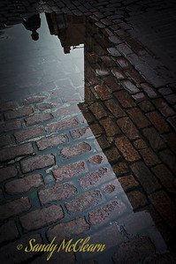 Buildings and people reflect in a puddle on a cobblestone street in Old Montreal.