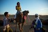 Roya boarding a camel.