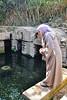 Rabat:  Woman feeding eels in Andalusian Gardens