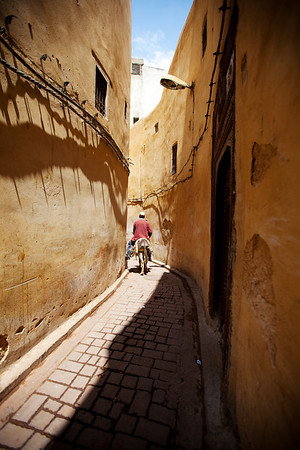 Man riding a donkey in narrow street in the medina of Fez