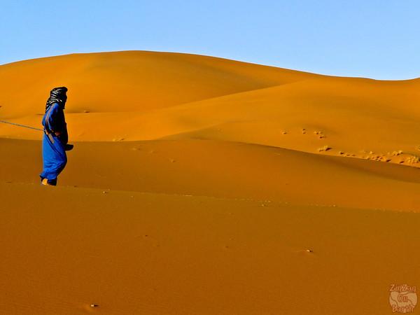 Berber  leading caravan in Sahara sand dunes