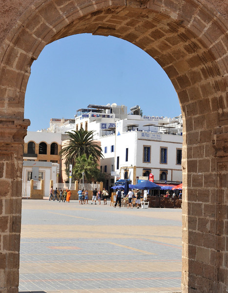Looking through a city gate to the harbour square, lined with cafes