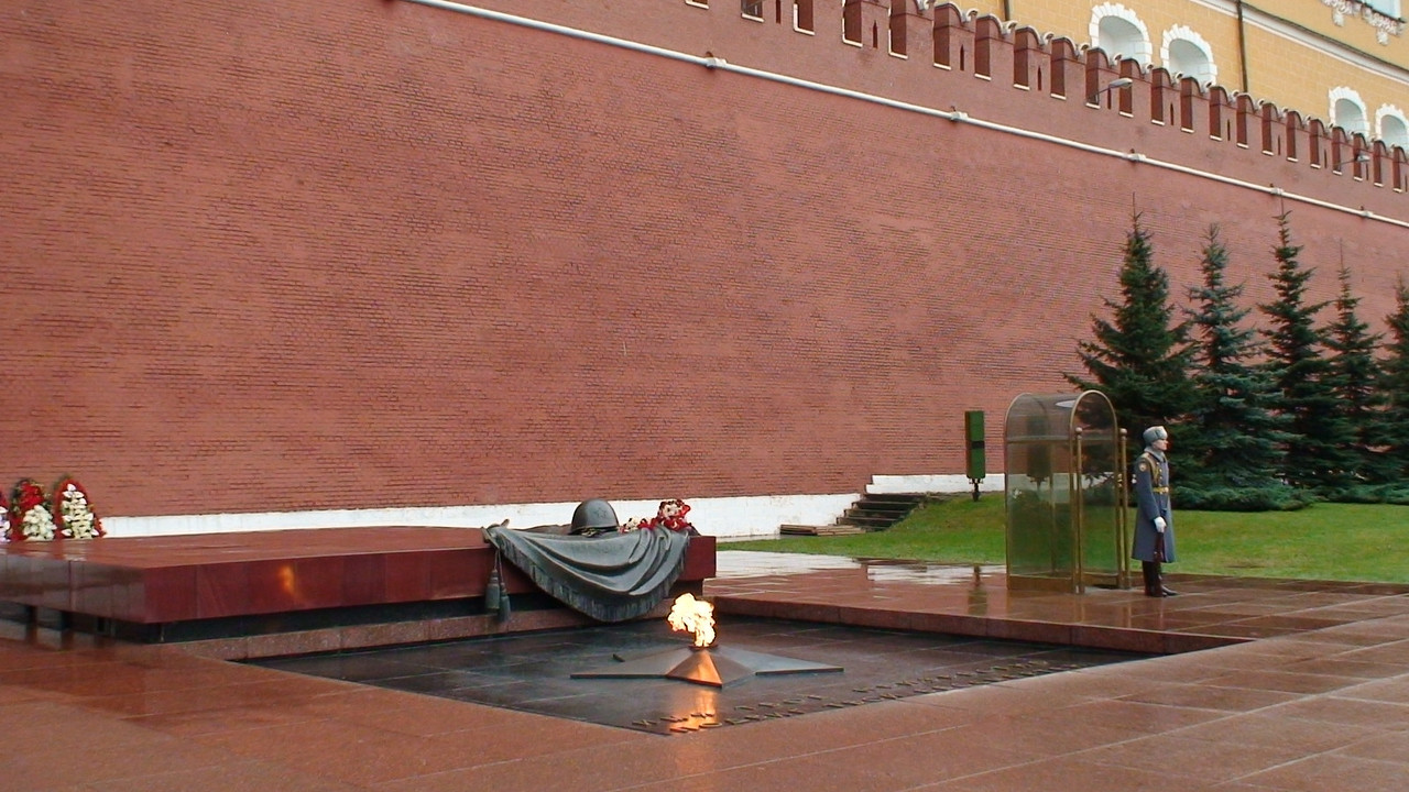 """The Tomb of the Unknown Soldier (Могила Неизвестного Солдата in Russian, or Mogila Neizvestnogo Soldata) is a war memorial, dedicated to the Soviet soldiers killed during the Great Patriotic War of 1941-1945. It is located at the Kremlin Wall in the Alexander Garden in Moscow.<br /> <br /> The remains of the unknown soldiers, killed in the Battle of Moscow in 1941 and initially buried in a mass grave at the 41st km of the Leningrad highway, were relocated to the Kremlin Wall in December of 1966 (25th anniversary of the battle). The Tomb of the Unknown Soldier was unveiled on May 8, 1967. The torch for the memorial's flame was transported from Leningrad, where it had been lit from the Eternal Flame at the Field of Mars.<br /> <br /> The centerpiece of the memorial is a platform, which consists of big plates made of polished red granite. The tombstone itself is decorated with a sculptural composition made of bronze (a laurel twig and a soldier's helmet lying on a banner; installed in 1975).<br /> <br /> In front of the tombstone, there is a five-pointed star in a square pit, which emanates the Eternal Flame of Glory from its center. The flame illuminates a bronze inscription saying """"Your name is unknown, your deed is immortal"""" (Имя твоё неизвестно, подвиг твой бессмертен, or Imya tvoyo neizvestno, podvig tvoy bessmerten).<br /> <br /> To the left of the tomb, there is a granite wall with an inlay saying """"1941 - To Those Who Have Fallen For The Motherland - 1945"""". To the right of the tomb, there is a granite alley made of porphyry plates with incapsulated soils from hero cities, Leningrad, Kiev, Volgograd, Odessa, Sevastopol, Minsk, Kerch, Novorossiysk, Tula and Brest.The plate for Volgograd has since been changed to Stalingrad, the city's name during the Second World War.<br /> <br /> In 1997, a Guard of Honour was restored at the Tomb of the Unknown Soldier by the order of the President of Russia."""
