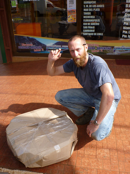 The cheap tires purchased in Paraguay were smuggled into Argentina and then put onto a bus to San Rafael (still much cheaper than finding tires in Argentina).  Here, Mike dripping sweat onto the irregular box.