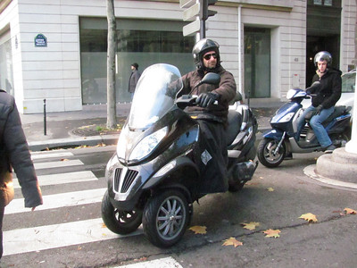 Another big bore Piaggio, businessman hamming it up...  They have these neat covers for their pants so they don't get wet in the chronic rain...
