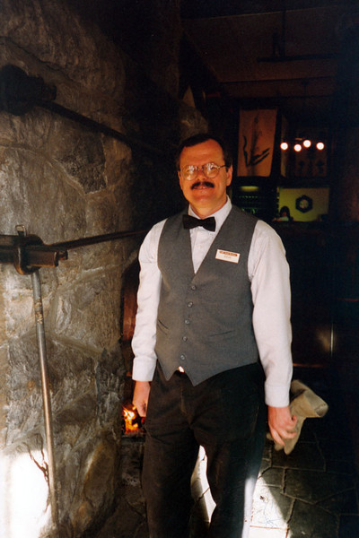 DOUG THE BELLMAN<br /> Having had my fill of being a Gift Shop Supervisor, I took on a job as a bellman at Paradise Inn. One of the fun duties of the job was building and maintaining fires in the two huge fireplaces at either end of the lobby, as you see me here.