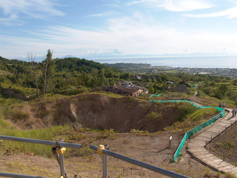 This is a second crater that opened up but is less active and only steaming slightly.  One of the unfortunate buildings that was a bit too close to the main eruption is just beyond the lip of the crater. The city of Toya in the background and the sea. Can you say Pompeii?