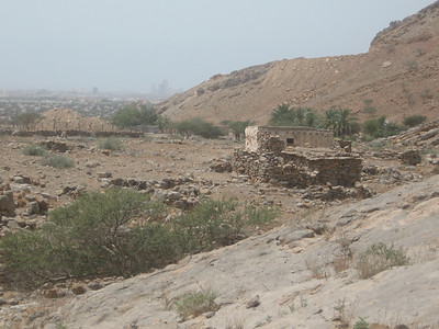 Looking back over an old stone house with RAK in the distance.