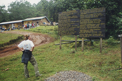 "Justine reading the ""points to remember"" at Machame gate entrance. Porters milling in background hoping for work."