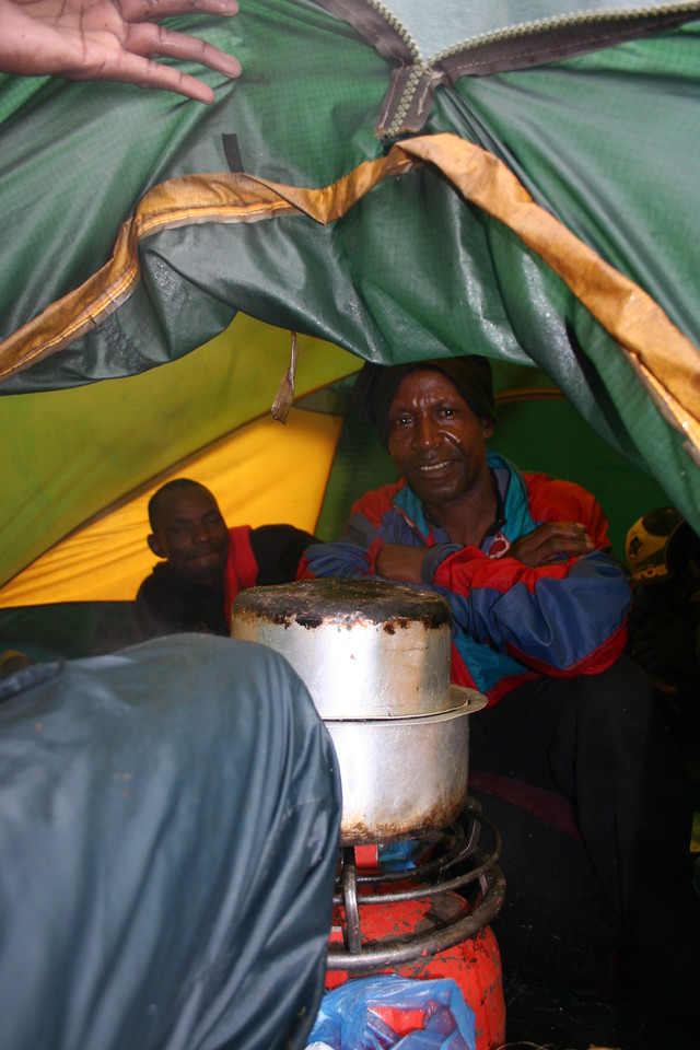 Cooking is a tiny tent, with a very big stove.