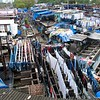 This is Dhobi Ghat. It is the world's largest open air laundry. It has 700 washing pens built of concrete and stones. The Dhobis wash the dirty clothes in soupy water and then they thrash them on stones, prior to air-drying them.