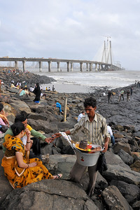 Couples having channa (peas) and seeng (peanuts) Bandra to Worli Sea Link in Mumbai during the monsoon rains. Mumbai, MH, India