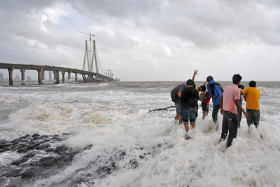 Kids having fun with the water splashing at the Bandra to Worli Sea Link in Mumbai during the monsoon rains. Mumbai, MH, India