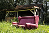 Abandoned couch in front of an abandoned shed.