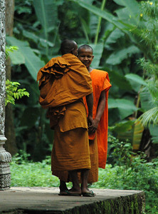 Two Buddhists monks at Angkor Thom, Cambodia trading confidences.