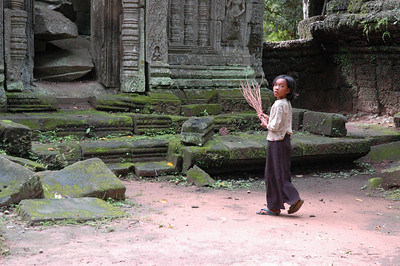 A local girl, broom in hand, employed to sweep the public areas of the Ta Phrom ruins, Angkor, Cambodia.