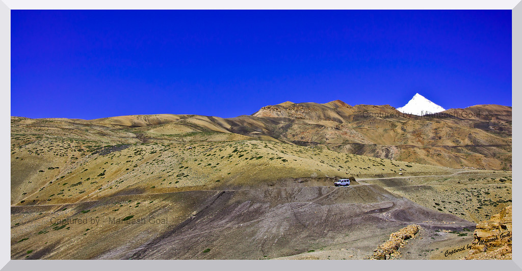 Drive through a cold desert, Spiti Valley (Himachal Pradesh). Snow clad Shila Peak can be seen on the right.